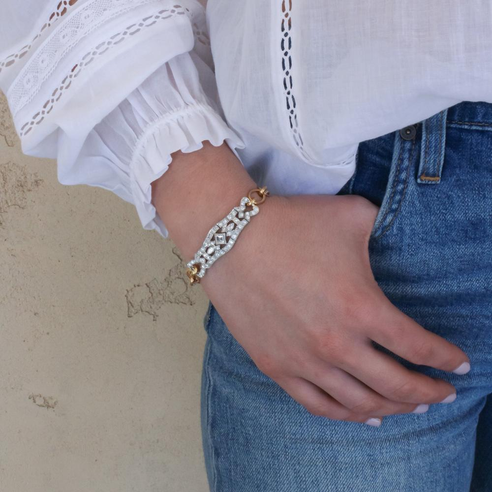 woman with blue jeans and white shirt with bracelet on arm