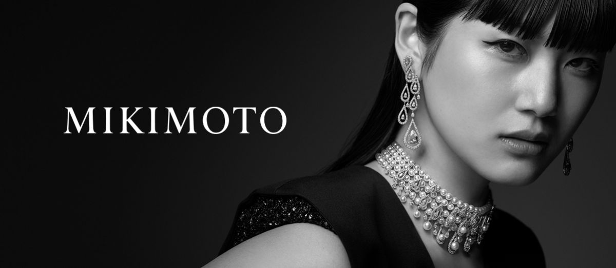 Black and white photo of a man and woman wearing pearls with white Mikimoto logo.