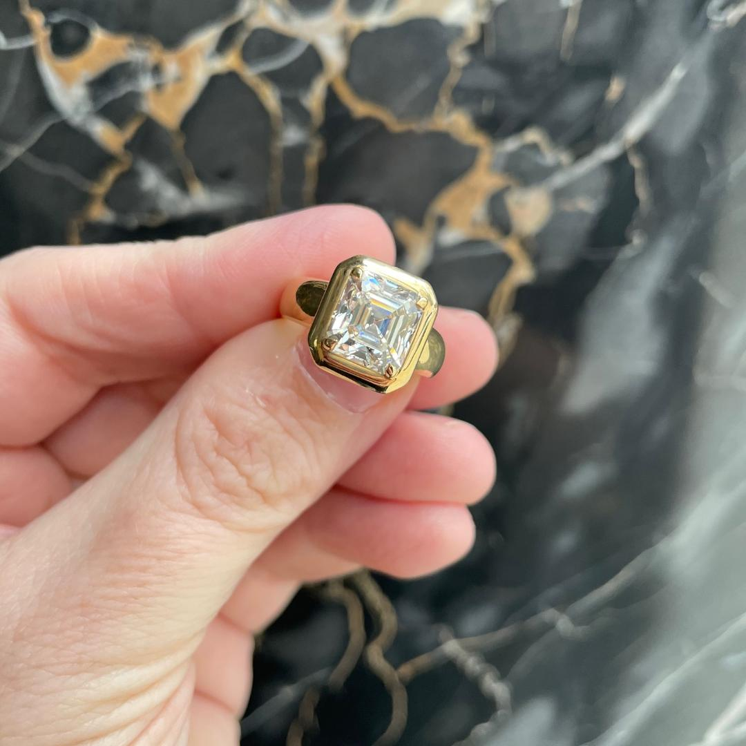 Square diamond ring in yellow gold being held against a dark marble background
