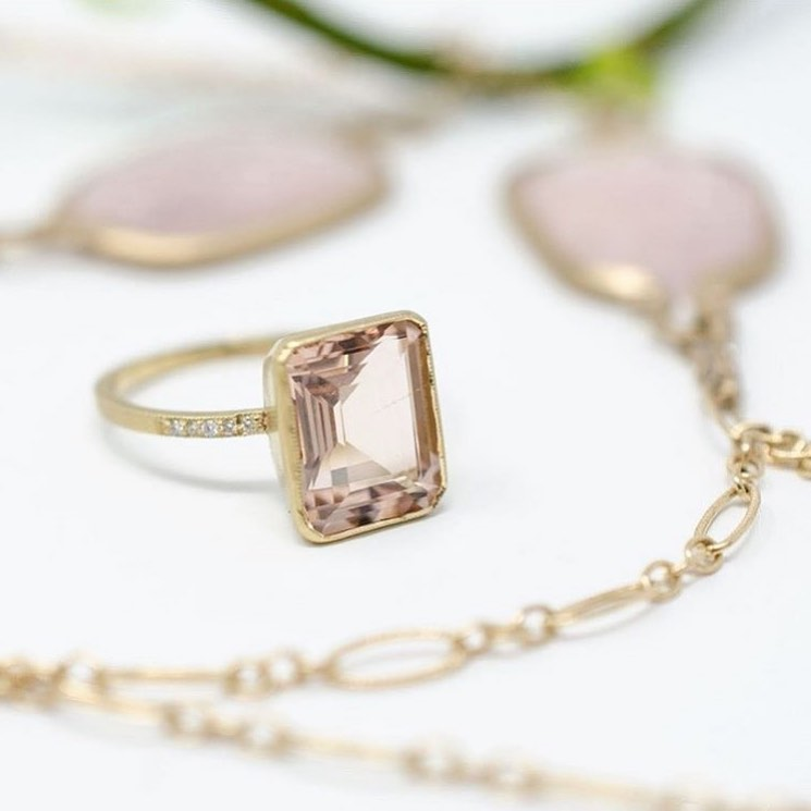 Jennifer Dawes morganite pink ring in rose gold with necklace draped around it.