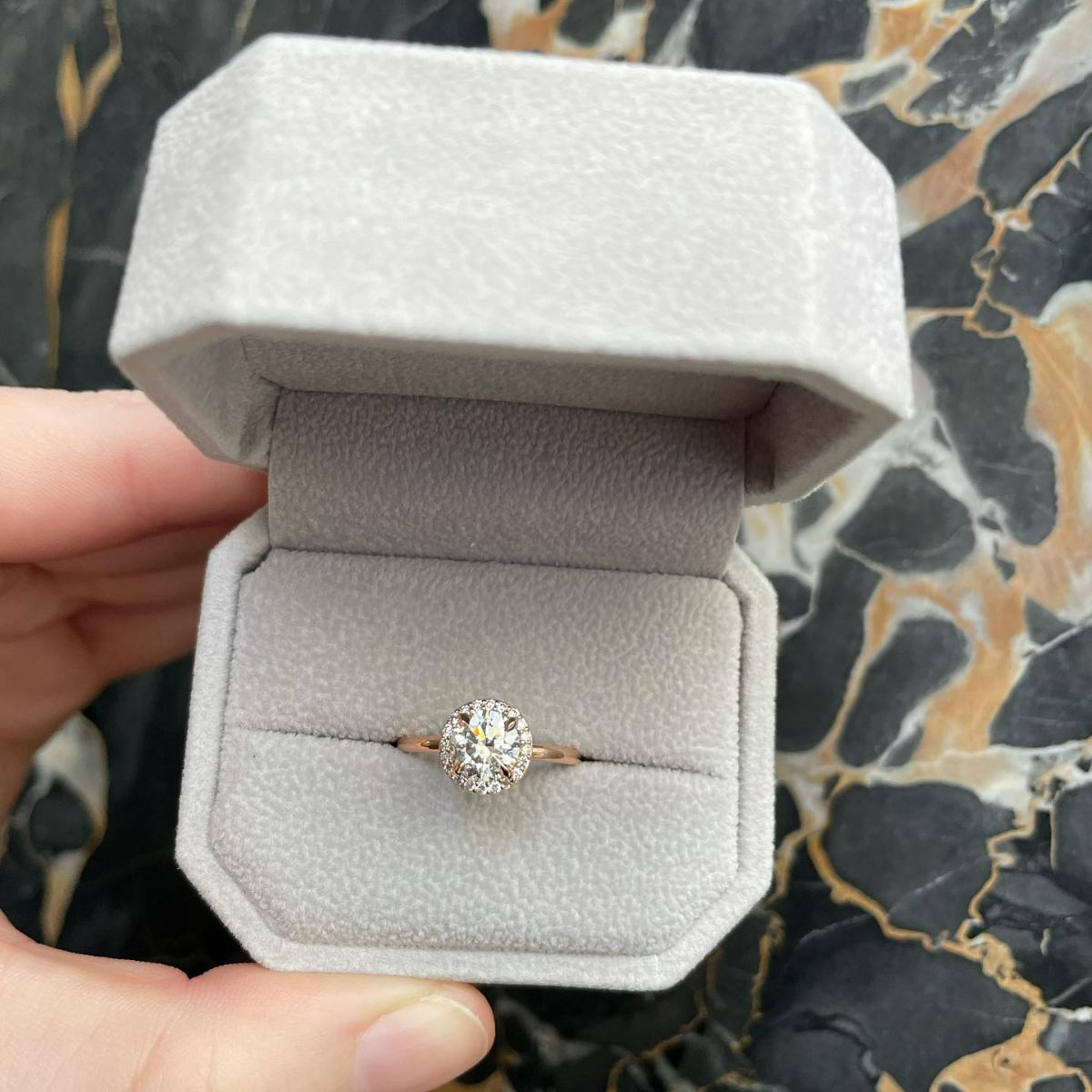 Link takes you to designer engagement rings. Photo shows ring box with round diamond engagement ring inside