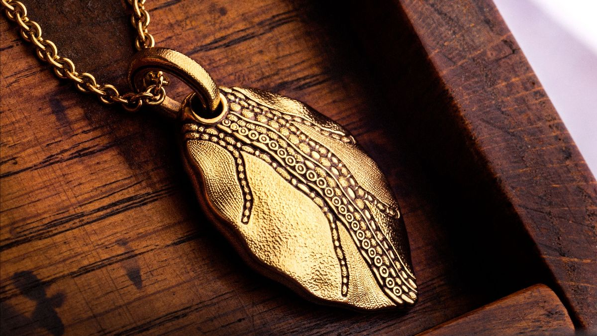 yellow gold leaf necklace on wood background