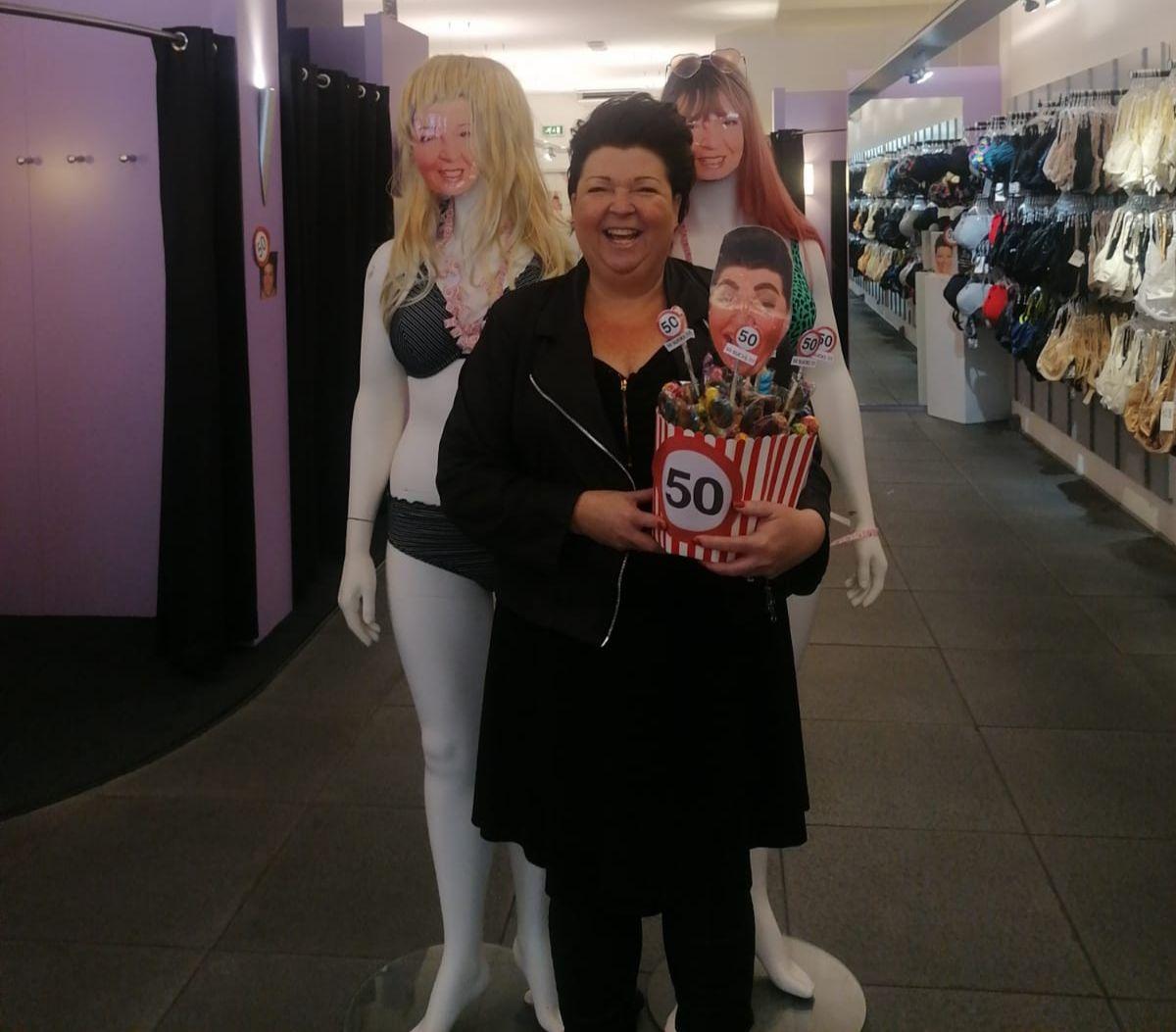 Sharon tussen twee paspoppen met haar gezicht, met cadeau in haar handen