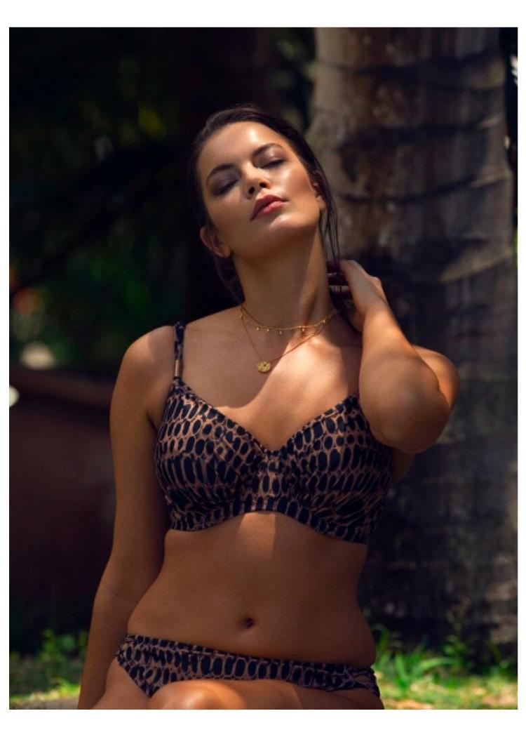 vrouwzittend in de schaduw met zon op gezicht in fantasie swim  kotu bikini