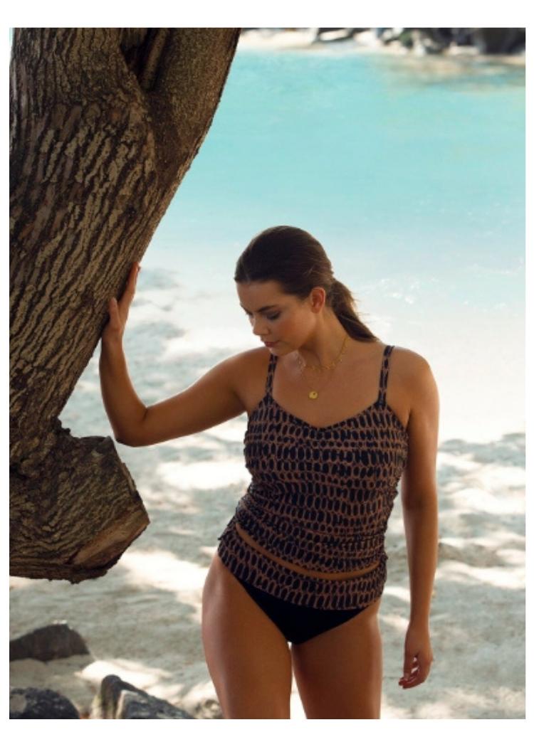 vrouw staat in de zee met hand tegen boomstam in fantasie swim kotu tankini