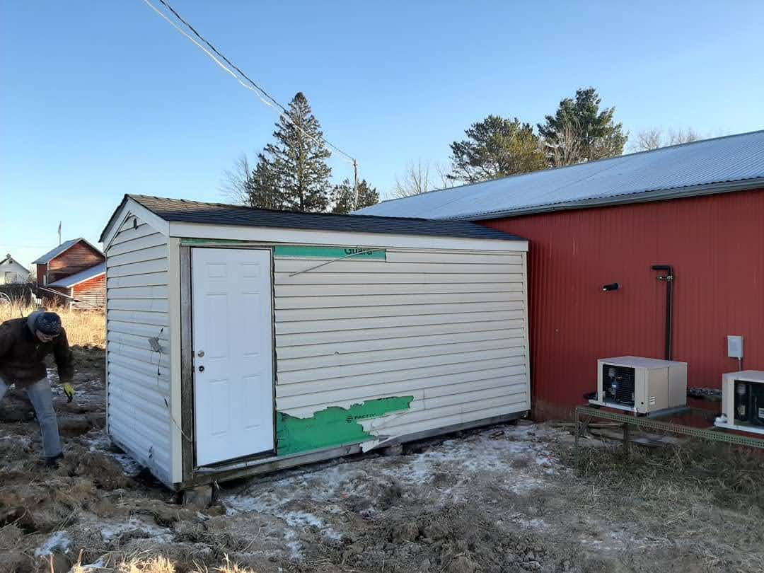 Other side of the shed, showing the door and torn up vinyl siding.