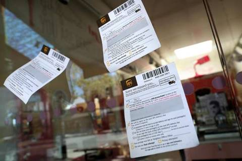 UPS delivery notices dot the windows of a beauty shop on a near-empty  Fourth Street in Berkeley, normally a bustling area during lunch hour.
