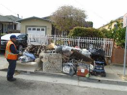 A person standing next to a pile of garbage    Description automatically generated with low confidence