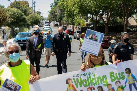 Richmond Police officers, Contra Costa County sheriffs, local community leaders and school board members walk through the Shields-Reid neighborhood of Richmond during a Walking School Bus event to promote safe streets for students traveling between Verde Elementary School and programs at Shields-Reid Community Center in Richmond, Calif. Monday, June 14, 2021. Richmond Police Chief Bisa French and her allies recently defeated a plan by Richmond's Reimagining task force to shift $10.3 million from the police budget to social services, which would have required laying off 35 officers.
