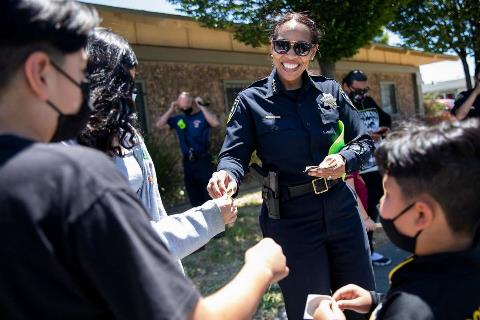 Richmond Police Chief Bisa French hands stickers out to local kids following a Walking School Bus event to promote safe streets for students traveling between Verde Elementary School and programs at Shields-Reid Community Center in Richmond, Calif. Monday, June 14, 2021. Richmond Police Chief Bisa French and her allies recently defeated a plan by Richmond's Reimagining task force to shift $10.3 million from the police budget to social services, which would have required laying off 35 officers.
