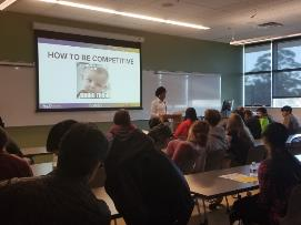 A person giving a presentation to a group of people    Description automatically generated with medium confidence