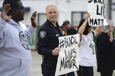 In this photo taken Tuesday, Dec. 9, 2014, Richmond Chief of Police Chris Magnus stands with demonstrators along Macdonald Ave. to protest the Michael Brown and Eric Garner deaths during a peaceful demonstration in Richmond, Calif. The Northern California police chief noted for his community policing efforts raised a few eyebrows when he joined a peaceful protest, holding a sign with the popular Twitter hashtag of 'blacklivesmatter.' Magnus said he attended to show the department's commitment to peaceful protest and that minority lives matter. (AP Photo/Bay Area News Group, Kristopher Skinner) Photo: Kristopher Skinner, Associated Press