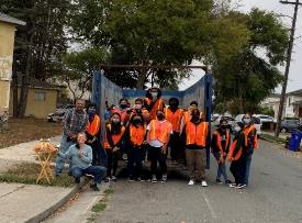 A group of people wearing orange vests and standing on the side of a street    Description automatically generated with low confidence