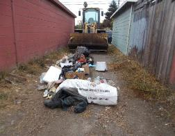 A person lying on the ground next to a pile of garbage    Description automatically generated with medium confidence