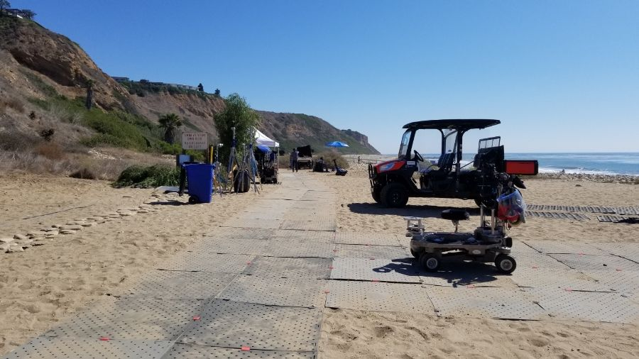 Image shows Access Trax pathway set up over sand at a private beach near a cliff. There are small vehicles parked near the pathway. This is at a Grey's Anatomy filming location.
