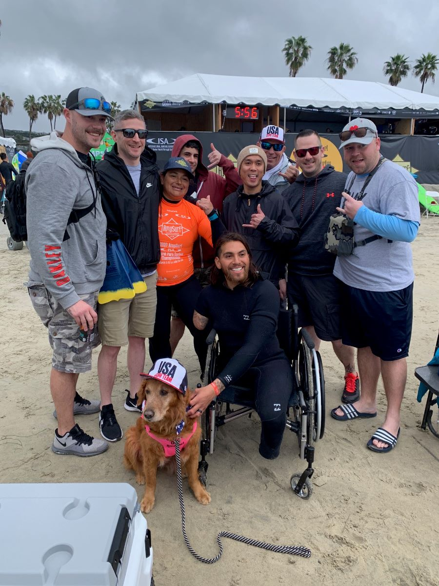 8 men and a woman pose for a photo on the beach with Surf Dog Ricochet seated in front. The  man in the center is Jose, a Veteran who is a triple amputee seated in his wheelchair wearing a wetsuit and smiling.