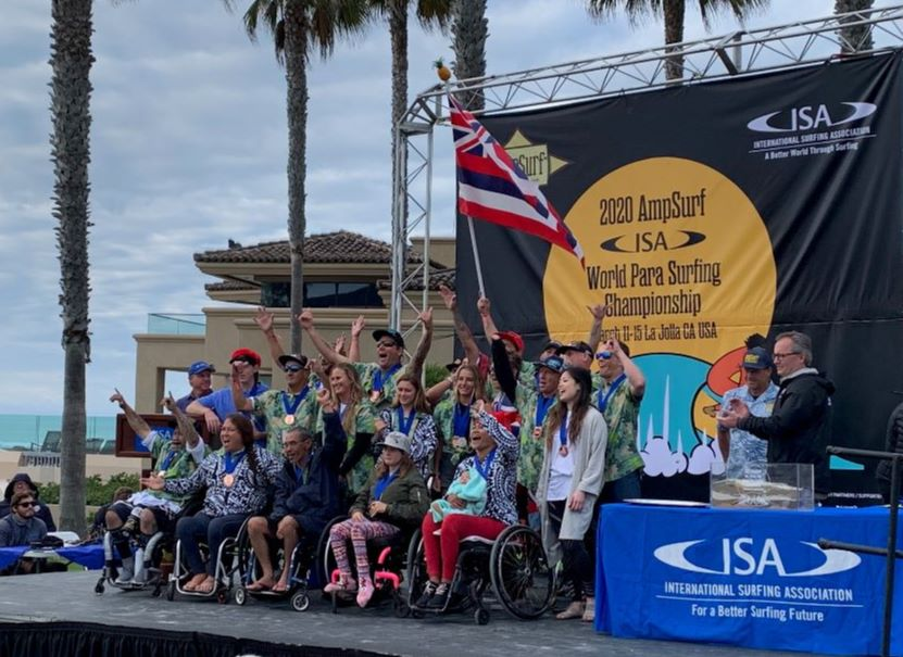 A group of adaptive surfers from Team Hawaii cheer on stage for a photo wearing their Copper Medals at the closing ceremony.