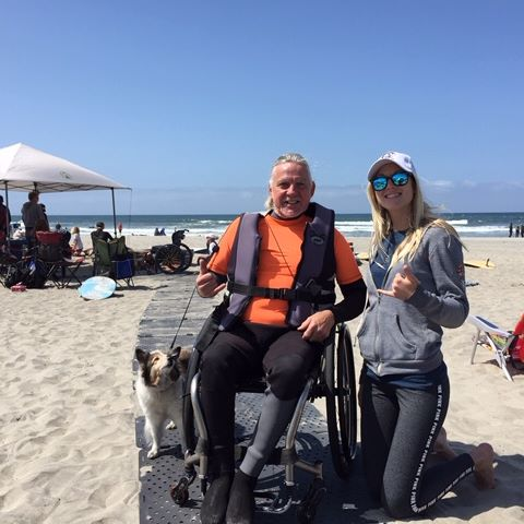 A man wearing a wetsuit seated in his wheelchair poses for a picture with a blonde woman wearing a hat at the beach. They are on the Beach Trax pathway. The man has his small dog on a leash.
