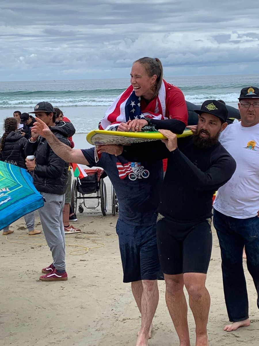 3 men carry a blonde adaptive surfer laying on her surf board draped in an American Flag coming in from the water. She is smiling after winning her heat.