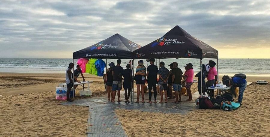A group of people stand on the grey Access Trax pathway over sand at the beach under pop up tents. The volunteers are meeting before the adaptive surfing event early in the morning.