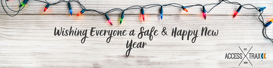 """A colorful string of holiday lights drapes the top of the banner image with a light colored wood grain background. Text reads: """"Wishing Everyone a Safe & Happy New Year."""" The Access Trax logo is in the bottom right corner."""