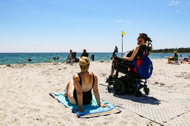 Image shows Kevin- a man seated in his power wheelchair wearing sunglasses and board shorts- and Dee- a woman sitting on a towel in her black one-piece bathing suit to the left of Kevin. They are at the beach and facing away from the camera, towards the blue water. Kevin's wheelchair is on top of the grey Access Trax pathway.