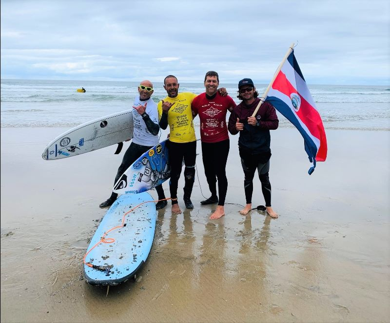 4 men wearing wet suits and colorful rash guards pose for a photo near the water before a surf heat. One man is holding a flag and there are 3 surf boards.