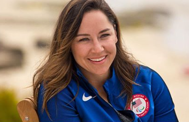 Head shot of a brunette woman smiling wearing a royal blue track jacket with the USA flag and Paralympic logo on it.