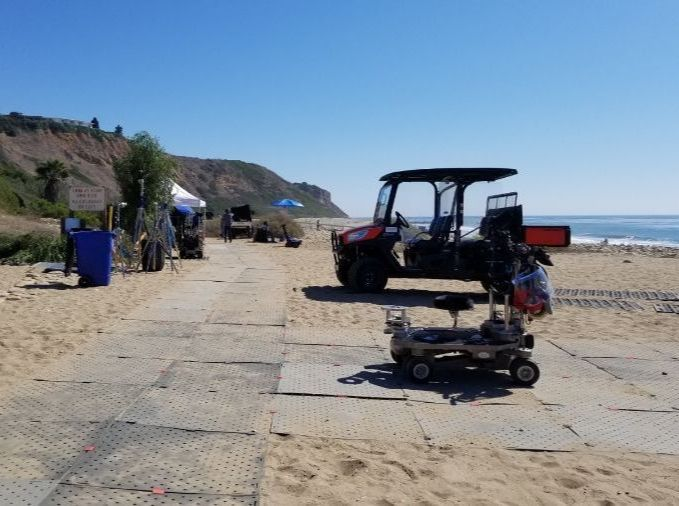 """Image shows the grey Access Trax pathway connected in a """"T"""" shape on sand at the beach with film equipment on it. There is a golf cart parked on the sand."""