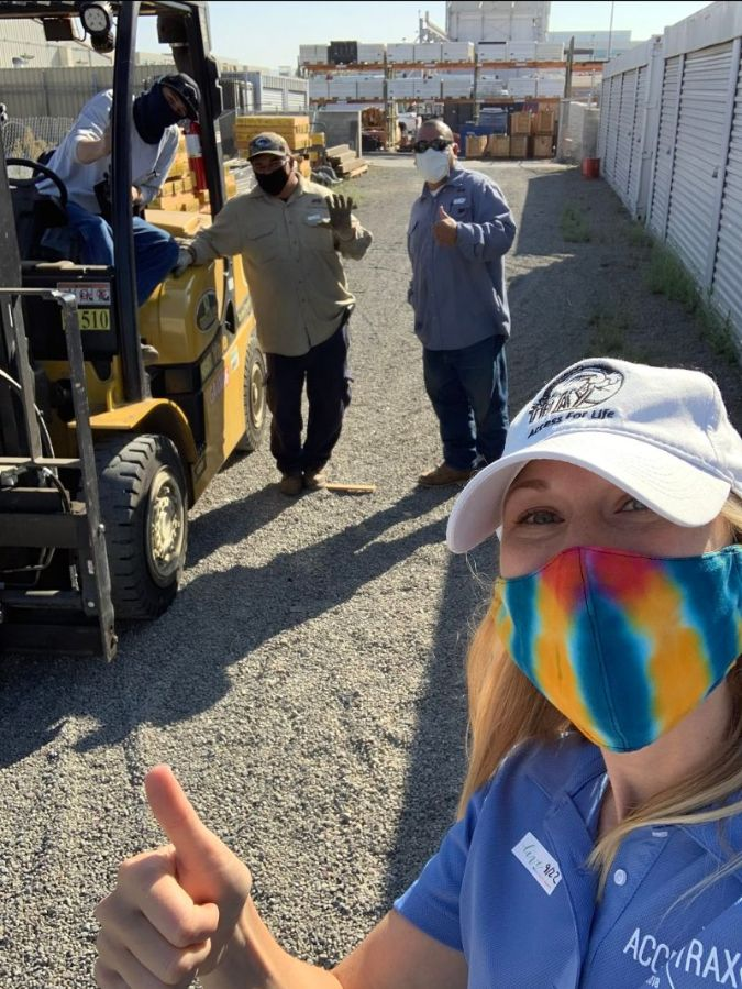 Image shows Kelly taking a selfie with 3 SDG&E team members behind her. One of them is seated in a forklift. They are on gravel.