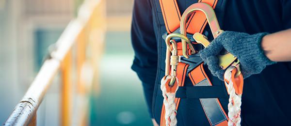 Travailleur de la construction portant un harnais de sécurité et attaché à un câble de sécurité pour travailler en hauteur.