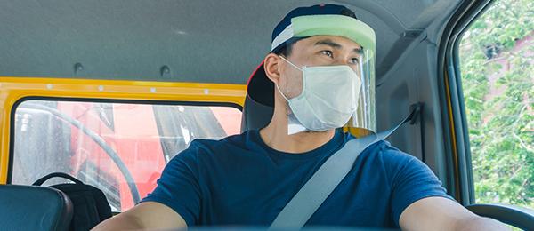 Homme portant un masque et un écran facial qui conduit un camion.