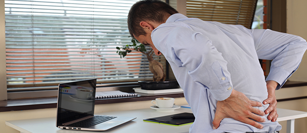 Homme assis à un bureau avec un ordinateur, se tenant le dos.