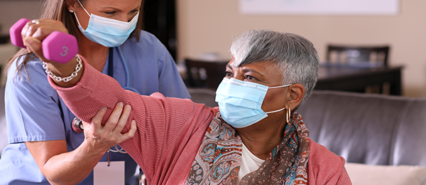 Femme âgée portant un masque médical bleu qui soulève un mini-haltère, assistée par un préposé portant un uniforme bleu et un masque.