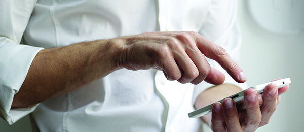 Man standing with up with a smartphone device, about to touch the smartphone screen with his finger.