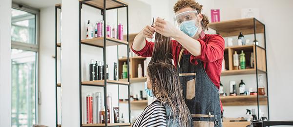 Jeune femme se faisant couper les cheveux chez le coiffeur pendant la pandémie, les deux personnes portant de l'équipement de protection.