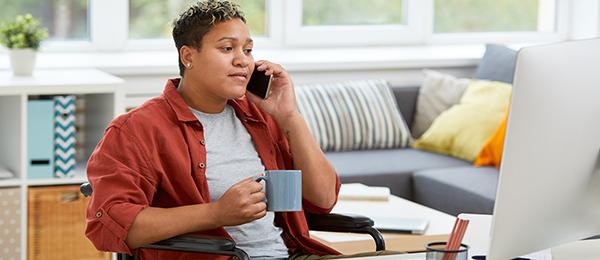 Femme en fauteuil roulant devant un ordinateur, buvant un café et parlant au téléphone.