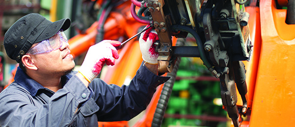 An automotive worker wears protective eye equipment while working on a machine.