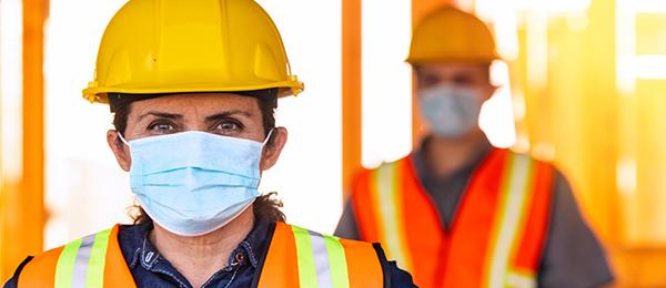 Deux travailleurs de la construction portant chacun un masque médical bleu, un casque jaune et un gilet de sécurité orange.