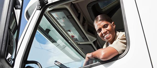Camionneuse afro-américaine assise dans la cabine d'un camion semi-remorque.