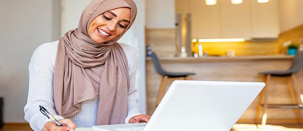 Femme souriante portant un foulard qui prend des notes et regarde un ordinateur portable dans un domicile.