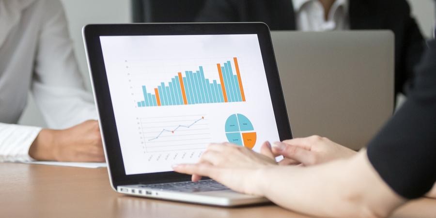 Persona mostrando gráficos estadísticos en su computador portátil