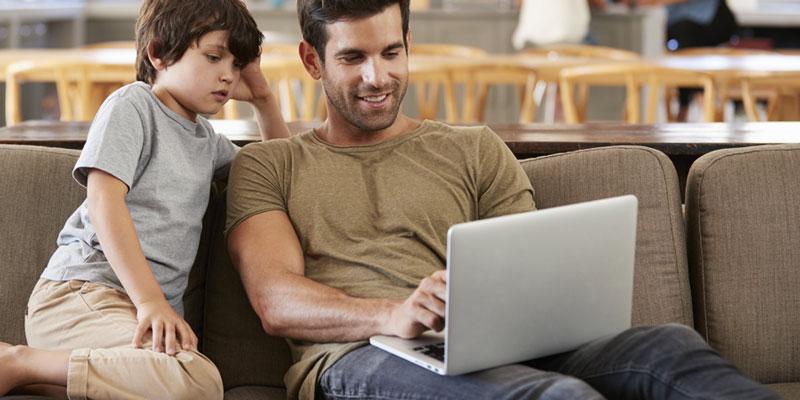 Padre utilizando ordenador portátil junto a su hijo