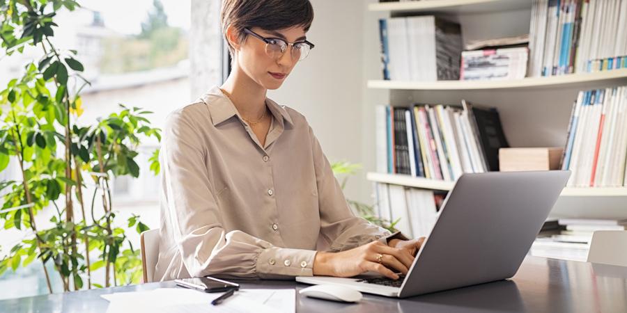 Mujer utilizando un computador portátil en su trabajo desde casa