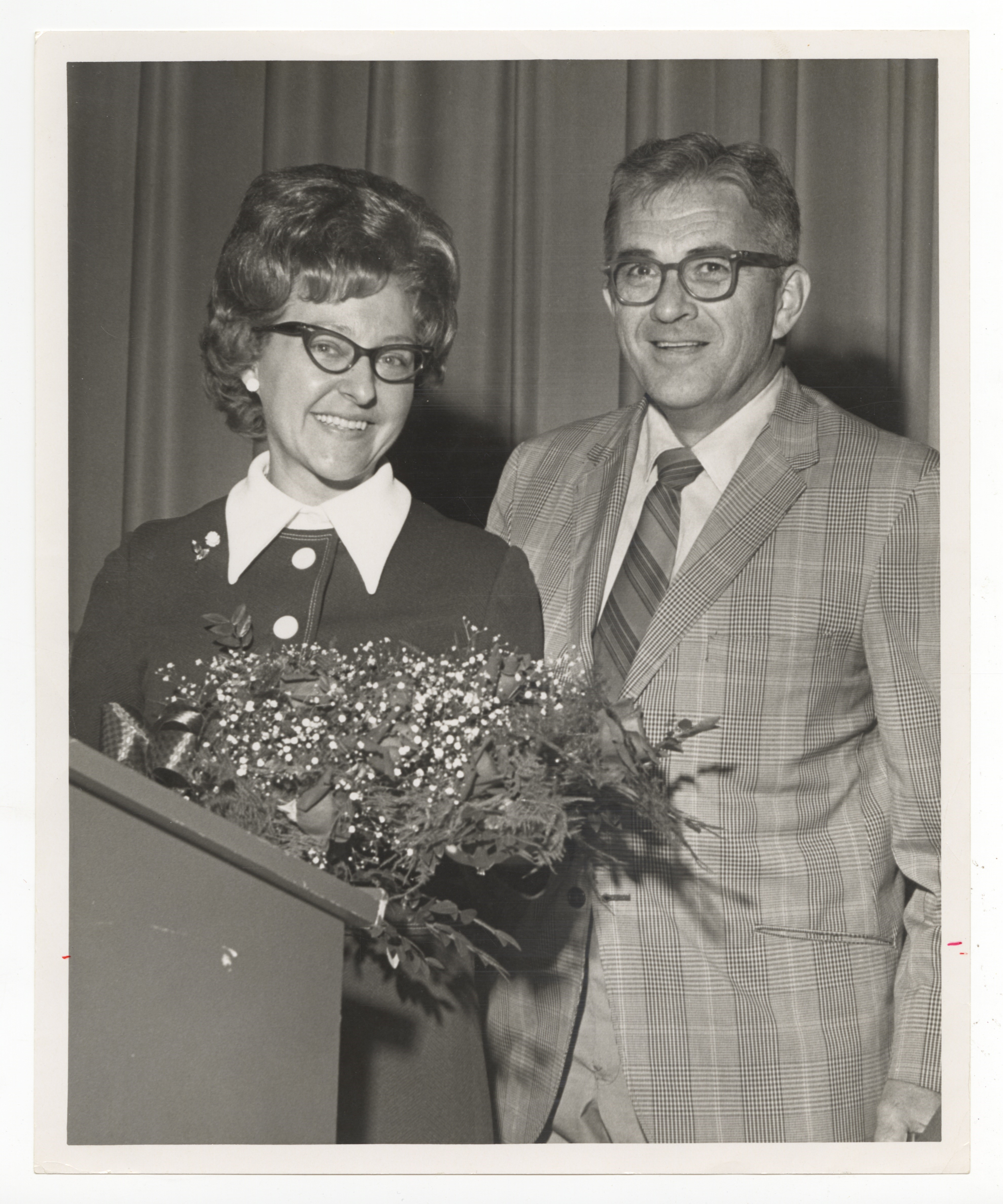 Pat Clapp, standing before a podium with a bouquet of flowers in April 1971. Pat's husband, Harry Clapp, is standing beside her. Patricia Clapp Papers and Photographs, MSS 1196, Detre Library and Archives, Heinz History Center.