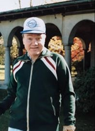Joe Benedum Trees in a warmup jacket and a ballcap standing in front of a building with archways
