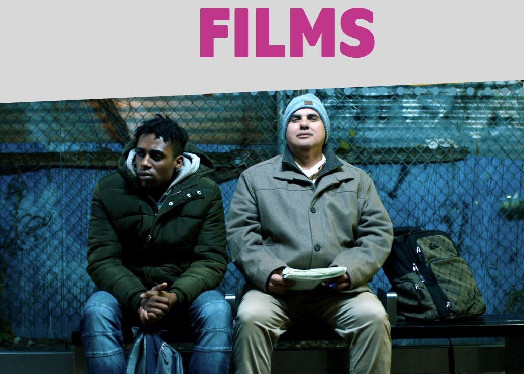 Still image from film trailer, two men of different races sitting on a bench. A brick urban wall with graffiti behind them.
