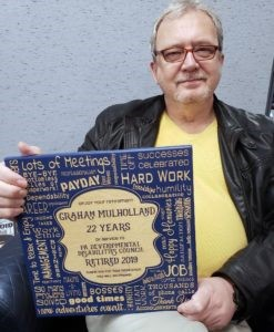 Graham Mulholland holding a retirement plaque that celebrates 22 years of service.