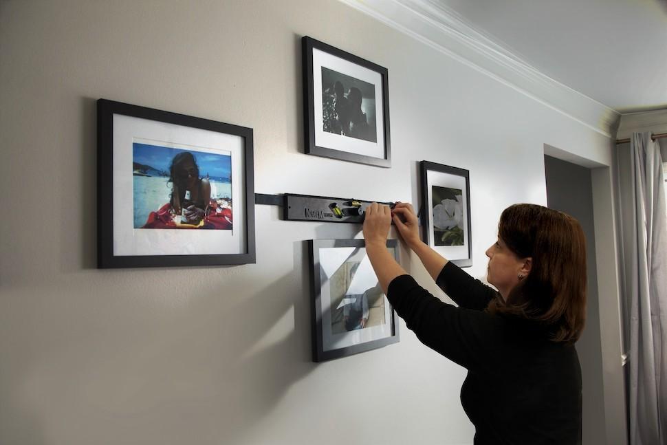 Woman hanging photos using NeverMeasure tool