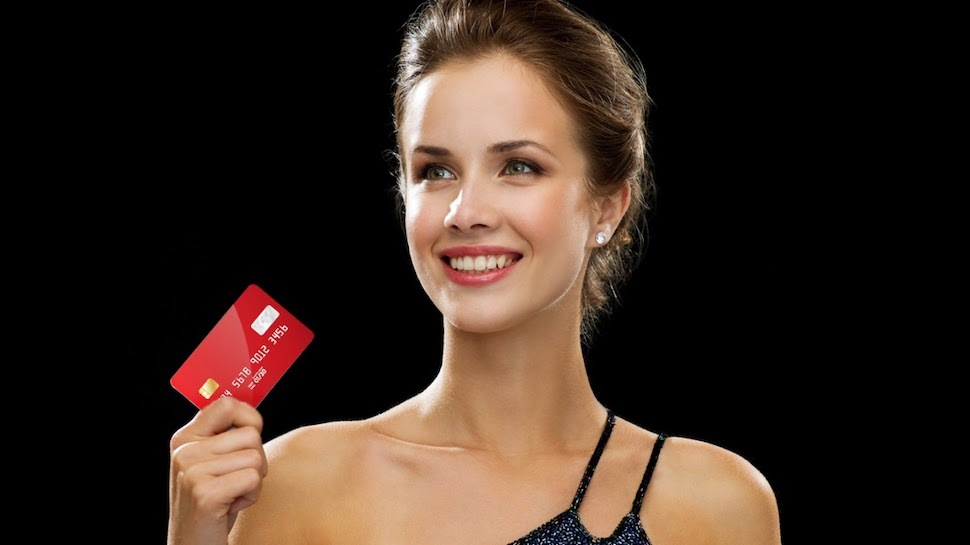 Woman holding a credit card in front of a black background